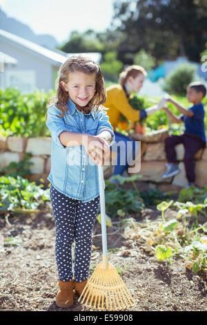 Girl holding rake in garden - Stock Photo