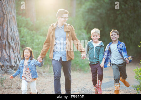 Students and teacher walking in forest - Stock Photo