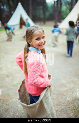 Girl smiling in sack at campsite - Stock Photo