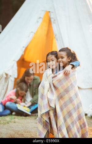 Girls wrapped in blanket at campsite - Stock Photo