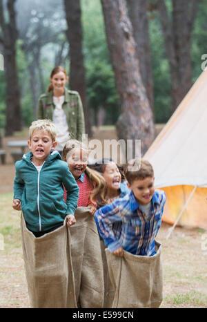 Children having sack race at campsite - Stock Photo