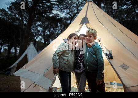 Children hugging by teepee at campsite - Stock Photo