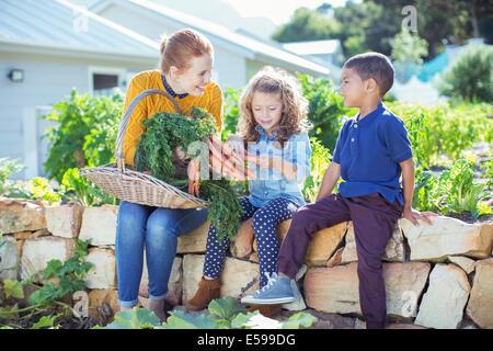 Teacher and students in vegetable garden - Stock Photo