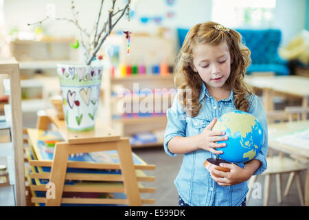 Student examining globe in classroom - Stock Photo