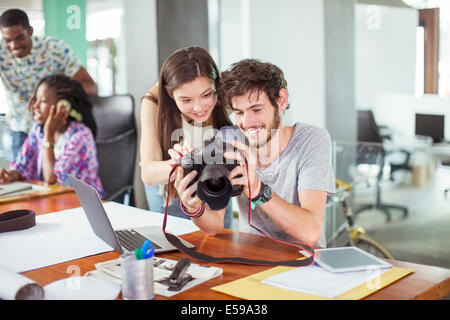 People reviewing photos together in office - Stock Photo