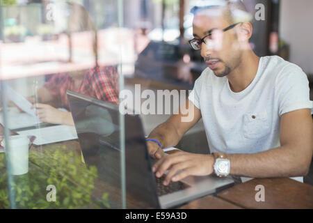 Man using laptop in cafe - Stock Photo
