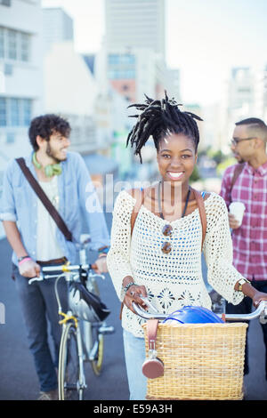 Friends pushing bicycles on city street - Stock Photo