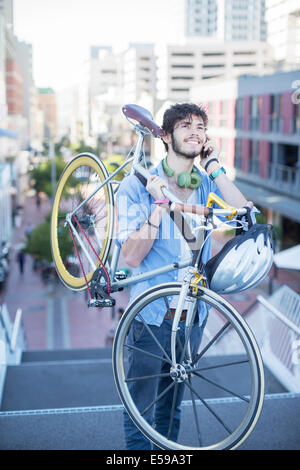 Man carrying bicycle on city steps - Stock Photo
