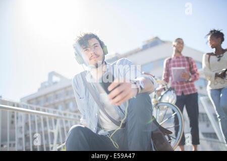Man listening to headphones on city street - Stock Photo