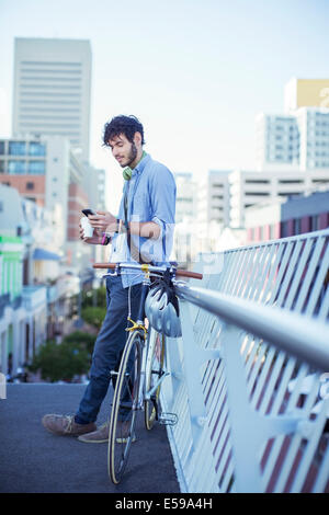 Man using cell phone on city street - Stock Photo