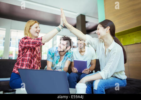People high fiving in office - Stock Photo