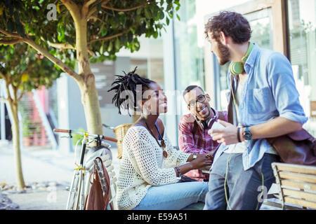 Friends talking on city street - Stock Photo