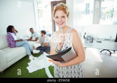 Woman carrying folders on city street - Stock Photo