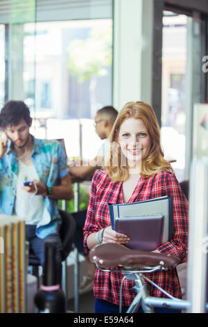 Woman carrying folders in cafe - Stock Photo