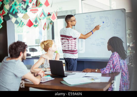 Man drawing on white board for colleagues - Stock Photo