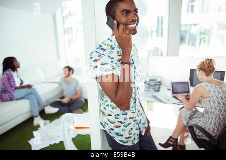 Man talking on cell phone in office - Stock Photo