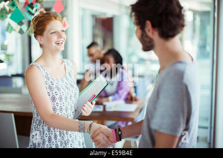 People shaking hands in office - Stock Photo