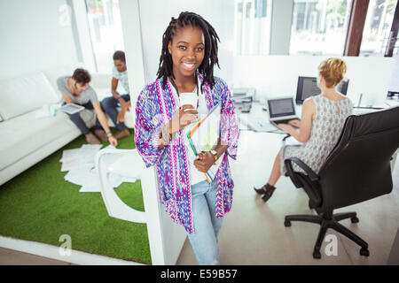 Woman drinking coffee in office - Stock Photo