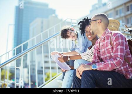 Friends sitting on city steps - Stock Photo