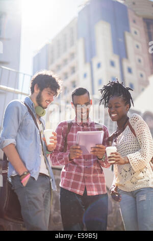 Friends using digital tablet on city street - Stock Photo