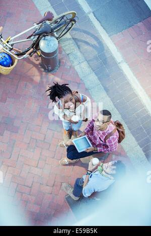 Friends using digital tablet on city street - Stock Photo