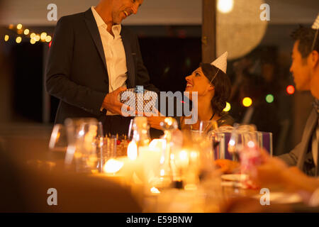 Man giving wife gift at birthday party - Stock Photo