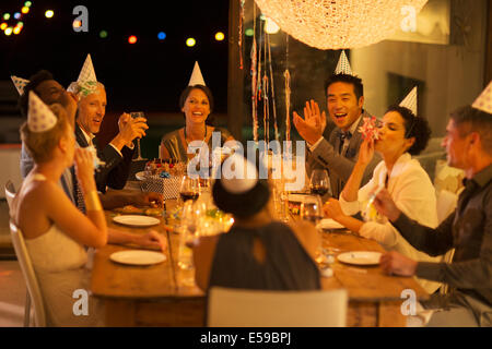 Friends cheering at birthday party - Stock Photo