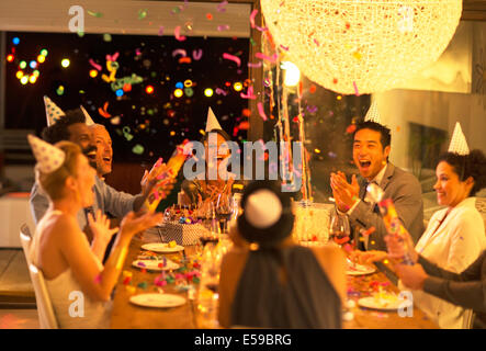Friends throwing confetti at birthday party - Stock Photo