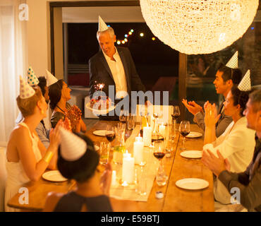 Man serving birthday cake at party - Stock Photo