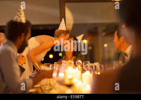 Woman kissing friend's cheek at birthday party - Stock Photo