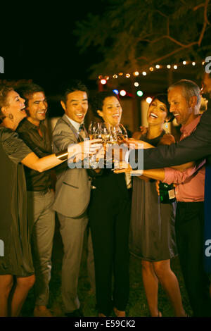 Friends toasting each other at party - Stock Photo