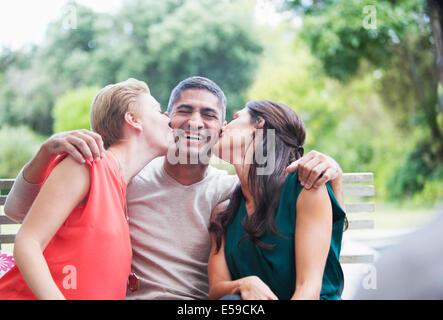Women kissing man's cheeks outdoors - Stock Photo