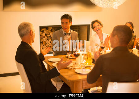 Friends applauding at dinner party - Stock Photo