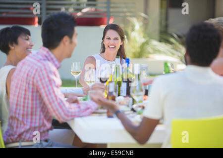 Friends relaxing together at table outdoors - Stock Photo