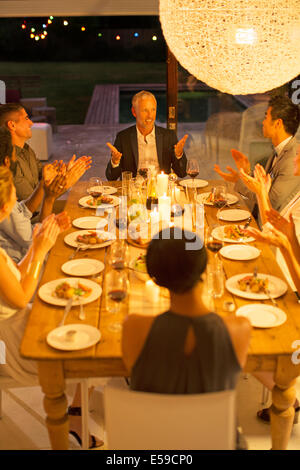 Friends applauding man at dinner party - Stock Photo