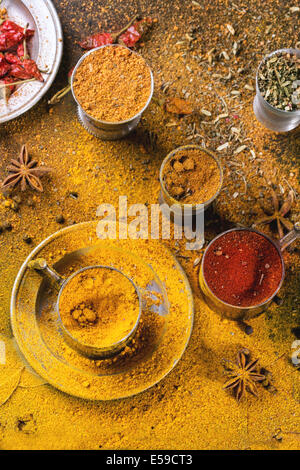 Set of spices pepper, turmeric, anise, coriander in vintage metal cups over yellow curry powder. Top view. - Stock Photo