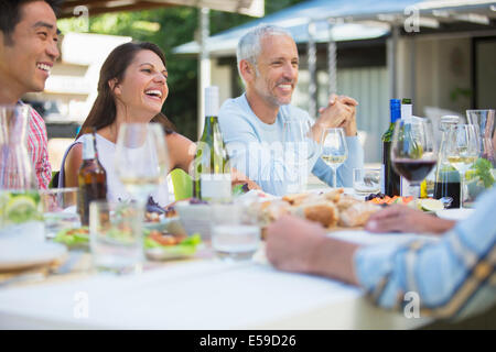 Friends talking at table outdoors - Stock Photo