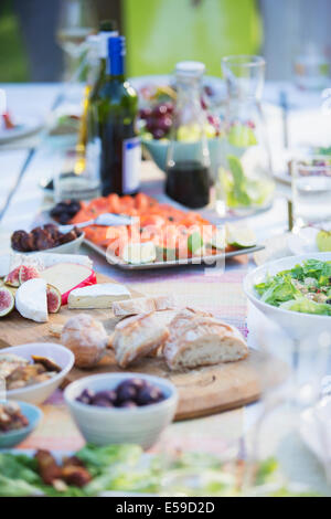 Plates of food on table outdoors - Stock Photo