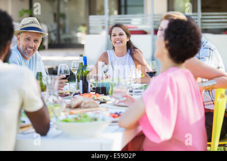 Friends relaxing at table outdoors - Stock Photo