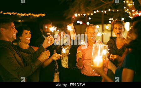 Friends playing with sparklers at party - Stock Photo