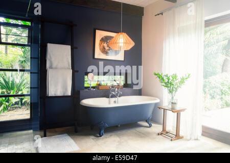 Bathtub and light fixture in modern bathroom - Stock Photo
