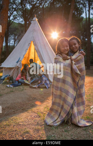 Children wrapped in blanket at campsite - Stock Photo