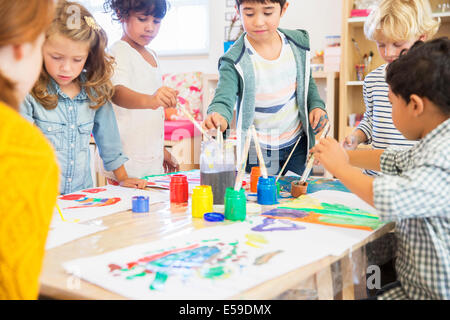 Students painting in classroom - Stock Photo