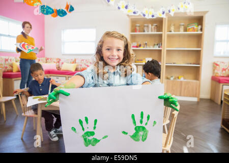 Student holding finger painting in class - Stock Photo