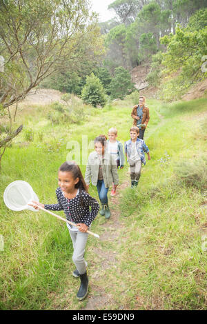 Students and teacher walking on dirt path - Stock Photo
