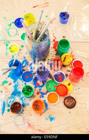 Jars of paint and paintbrushes on wooden table Stock Photo