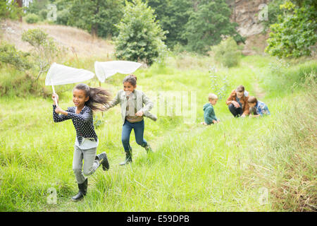 Children playing with butterfly nets on dirt path - Stock Photo