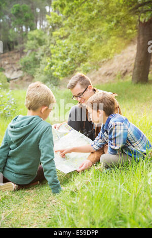Students and teacher reading map in field - Stock Photo
