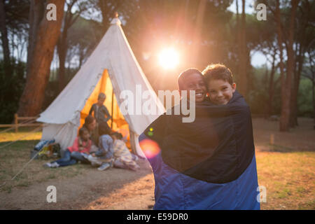 Boys wrapped in blanket at campsite - Stock Photo