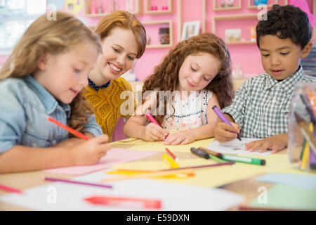 Students and teacher drawing in classroom - Stock Photo